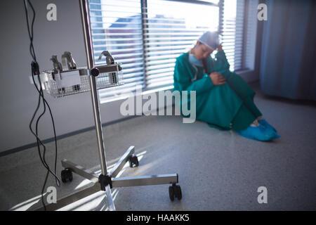Tensed female surgeon sitting in corridor - Stock Photo