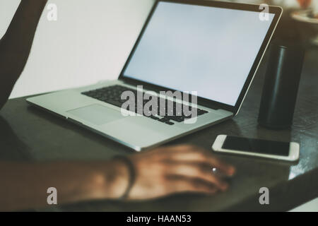 View of hands of a man working with modern laptop standing on concrete table of cafe, mobile phone and portable - Stock Photo
