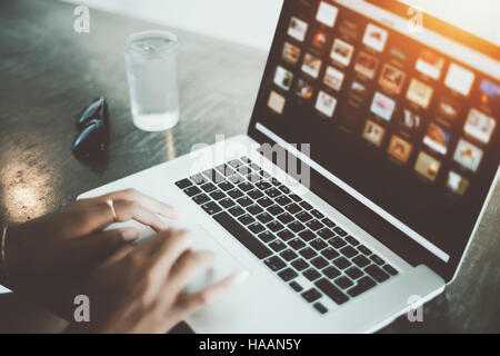 Close up view of woman hands using laptop on a stone table with glass of water and sunglasses behind, bright cafe - Stock Photo