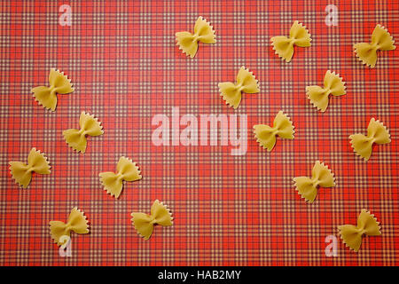 Pasta pattern background. Wholemeal bow tie farfalle on red squared tablecloth. Flat lay. Top view. - Stock Photo