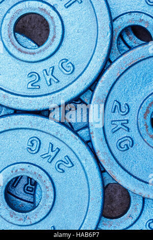 Blue weight plates of 2 kilograms stacked in an alternating pattern. - Stock Photo