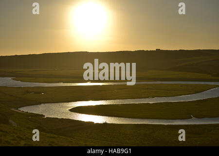 Cuckmere Haven, East Sussex. The sun setting over the iconic meanders of the Cuckmere river in the South Downs national - Stock Photo