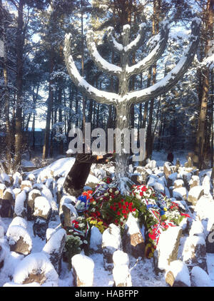 Rumbala, Latvia. 29th Nov, 2016. Visitors lay flowers by a large menorah monument at an memoral for the victims - Stock Photo