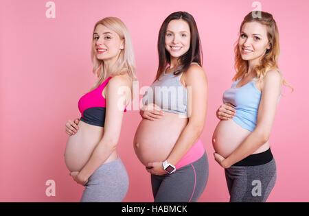 Three young moms smiling in the camera - Stock Photo