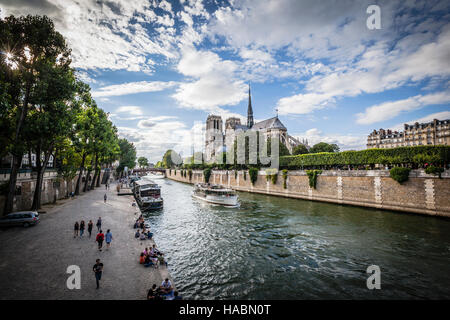 Notre Dame cathedral with puffy clouds, Paris, France - Stock Photo
