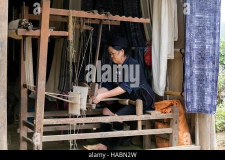 Black Hmong woman weaving on a loom in Cat Cat village, Sapa, Vietnam, Asia - Stock Photo