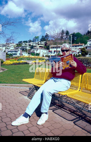 Middle-Aged Woman sitting on a Bench Outside and reading a Book, White Rock, BC, British Columbia, Canada - Stock Photo