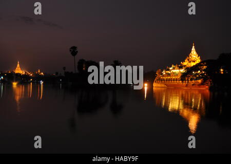 Lake Kandawgyi with illuminated Karaweik palace and Shwedagon pagoda at night - Stock Photo