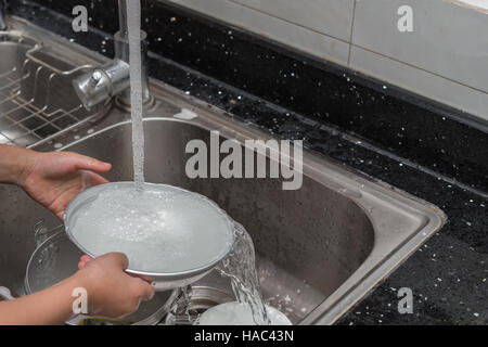 kid washing dishware in the kitchen sink with soapy sponge - Stock Photo