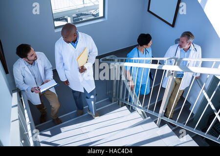 Doctors interacting with each other while climbing stairs - Stock Photo