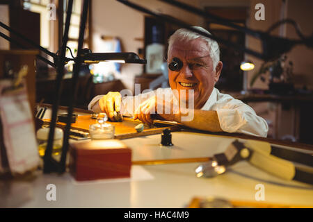 Horologist repairing a watch in the workshop - Stock Photo