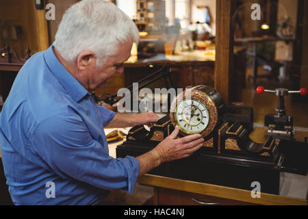 Horologist checking a clock in workshop - Stock Photo