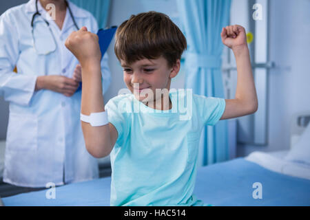 Boy flexing his muscles and female doctor standing in background - Stock Photo