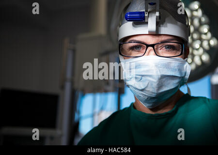 Portrait of female surgeon wearing surgical mask - Stock Photo