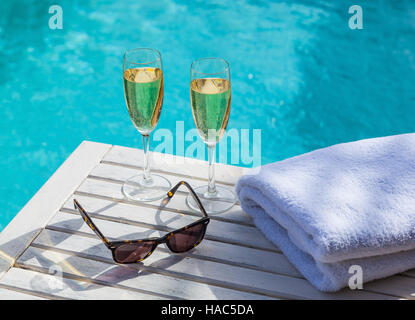 Two glasses of champagne on a white wooden table next to the swimming pool in summer. - Stock Photo