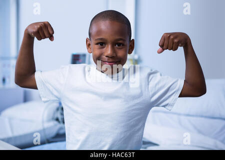 Portrait of boy flexing his muscles in ward - Stock Photo
