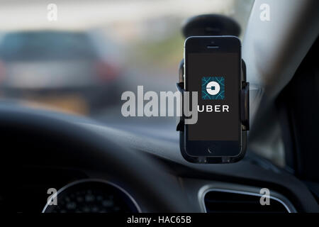 The interior of an Uber taxi with an iPhone fixed to the car's windscreen featuring the company logo. - Stock Photo