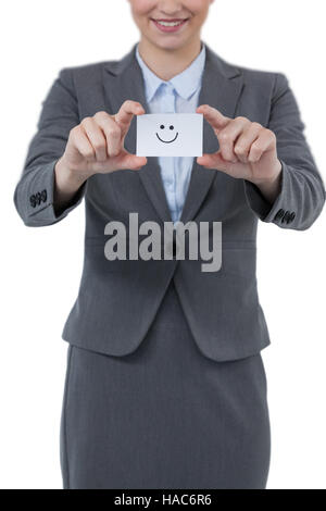 Businesswoman holding visitor card with smiley - Stock Photo