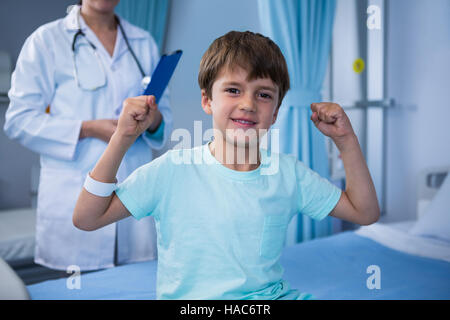 Portrait of boy flexing his muscles and female doctor standing in background - Stock Photo