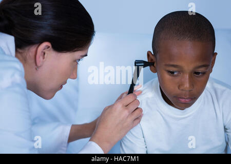 Female doctor examining patient ear with otoscope - Stock Photo