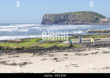 Sunny day with waves and blue sky at Torres, Rio Grande do Sul. Cliffs in background. - Stock Photo