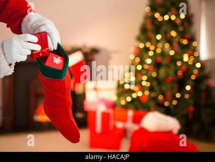 Santa Claus putting gifts in Christmas stocking - Stock Photo