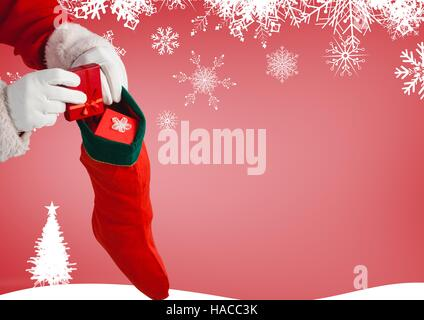 Santa claus putting gifts in christmas stockings - Stock Photo