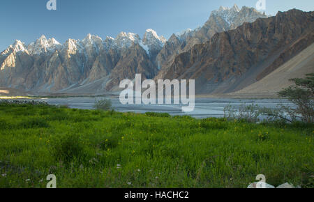 magnificent Tupopdan peaks and meadow along Hunza river in Passu, northern Pakistan - Stock Photo