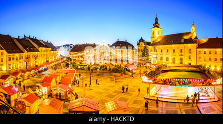 Sibiu, Romania. Night image with tourists at Christmas Market in Great Market of medieval Sibiu, Transylvania landmark. - Stock Photo