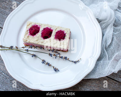 Raw cashew cake (cheesecake) and berries (strawberries, cherries), lavender on a wooden background. . Perfect for - Stock Photo