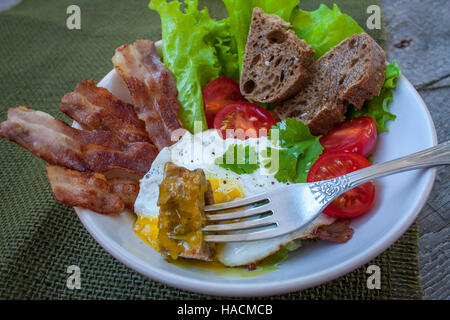 Classic hearty breakfast. Fried egg, bacon, vegetables (lettuce, tomato), greens and bread made from whole wheat - Stock Photo