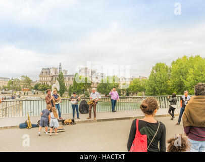 street musicians and tourists on pont saint-louis bridge, town hall (hotel de ville) in the background - Stock Photo