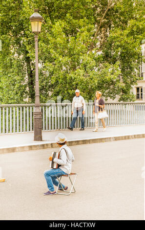 roma child street musician buskin on pont saint louis - Stock Photo