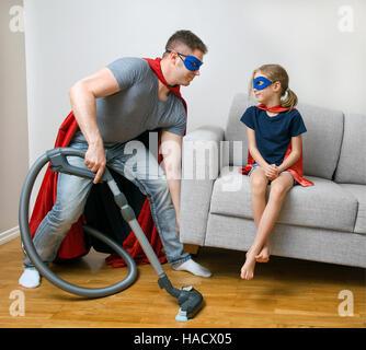 Ordinary day of superhero family. Dad doing housework. - Stock Photo