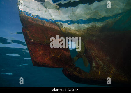 side view of bright coloured boat from underwater showing propeller and rudder. - Stock Photo