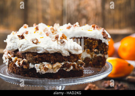 Homemade carrot orange cake with cream cheese frosting, traditional american afternoon tea treat - Stock Photo