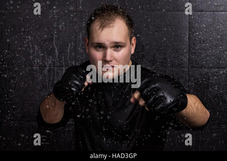 Portrait of boxer fighting in the rain in aquastudio with drops - Stock Photo