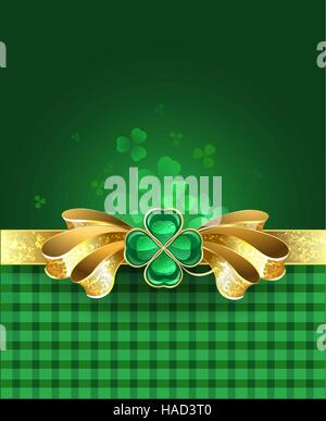 golden bow with a brooch in the form of a clover with four leaves on a green plaid background. - Stock Photo