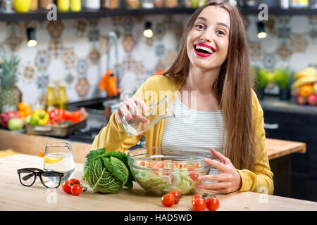Woman with salad in the kitchen - Stock Photo
