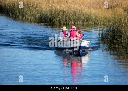 Uros people on boat near totora reeds field, Lake Titicaca, Puno, Peru - Stock Photo