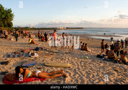 At dusk everyone gathers to watch the sunset with a beer on the beach of Kuta. Surfers on the beach of Kuta. Surfing - Stock Photo