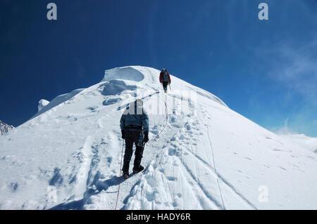 Mountaineers on summit ridge of Pisco mountain, 18897 ft / 5760 m, Peru, South America - Stock Photo