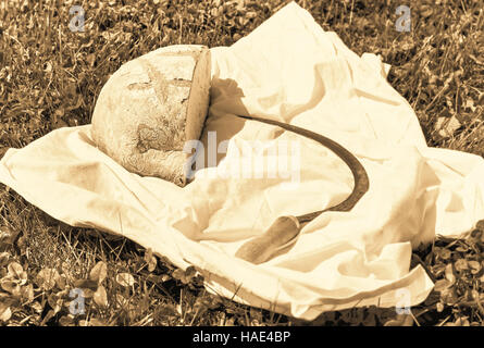 Loaf of bread and hammer on summer grass at sepia - Stock Photo