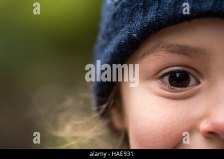 Young girl in warm blue wool hat. Half face of child in wooly winter hat smily with only eye fully in frame - Stock Photo