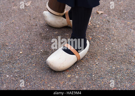 woman legs with a pair of pretty new wooden clogs with leather straps - Stock Photo