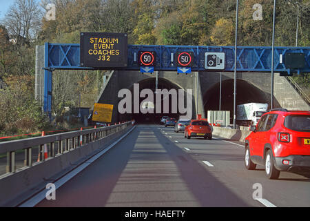 Looking towards the westerly bore of the M4 tunnel with a 50 mph restriction and other signs on a gantry over the - Stock Photo
