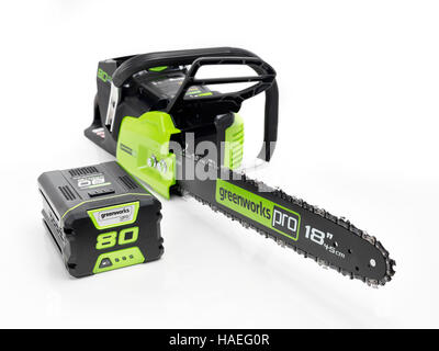 Electric Cordless chainsaw Greenworks and a large Lithium rechargeable battery isolated on white background - Stock Photo