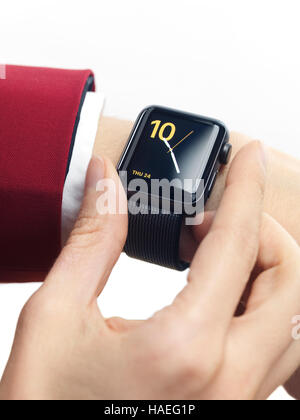 Woman hand in red suit with Apple Watch smartwatch on her wrist displaying clock isolated on white background - Stock Photo