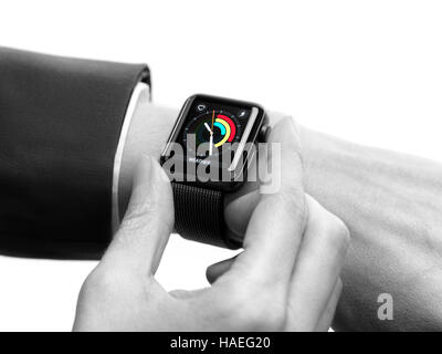 Woman hand with Apple Watch smartwatch on her wrist displaying daily activity and exercise isolated on white background - Stock Photo