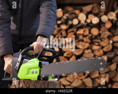 CLoseup of hands of a man holding an Electric Cordless chainsaw in front of stacked firewood in the background - Stock Photo